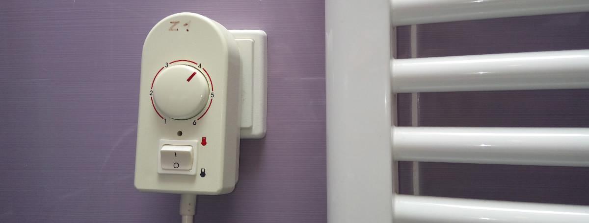 Na stene - elektrický nástenný radiátor, elektrická zásuvka, regulátor na elektrický radiátor
